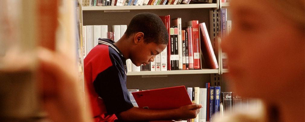 Young child reading a book in a library