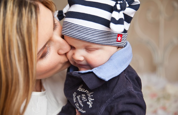 Baby being kissed by his mother
