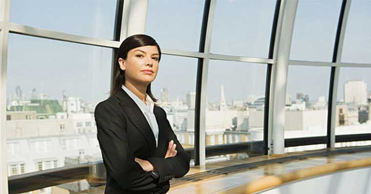 Business woman standing against the windows
