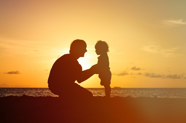 Father and child on the beach against a sunset