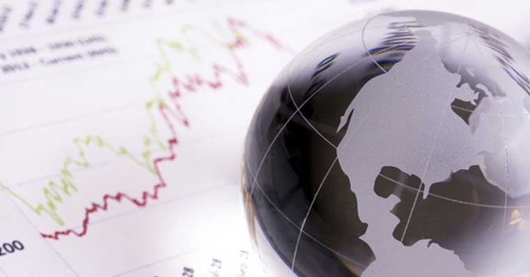 Globe sitting on paper with stock graphs