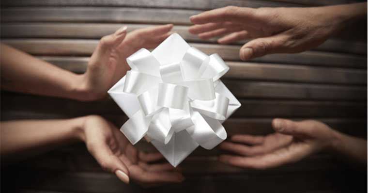 Hands holding a white gift together