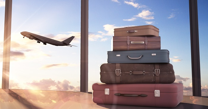 A stack of suitcases and an airplane taking off