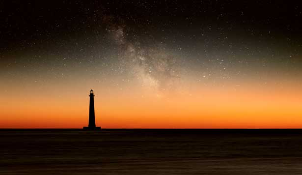 Lighthouse landscape at nighttime by the ocean