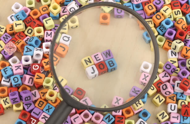 Letters spelling out new job under magnifying glass