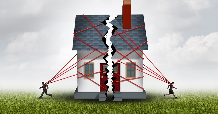 Two people breaking a house into two pieces