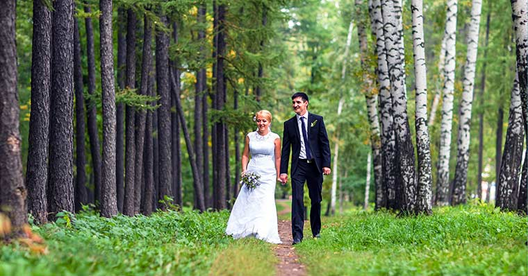 Wedding couple walking through the a forest