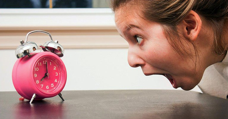 Woman screaming at an alarm clock