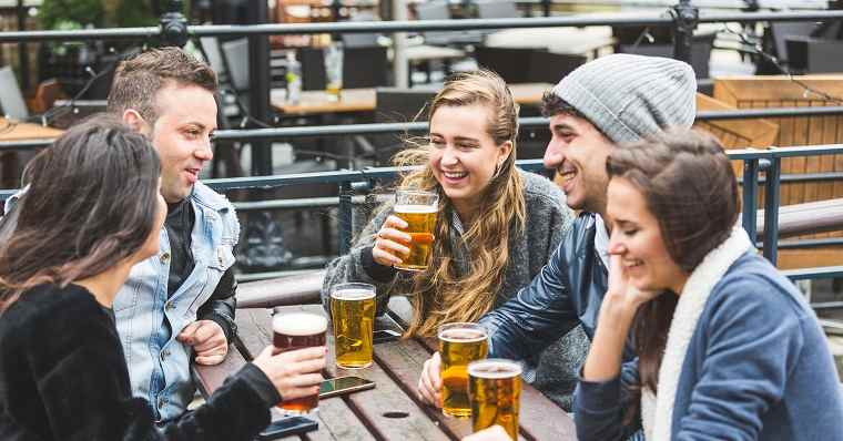 Young friends drinking beer at pub