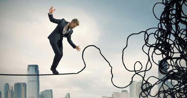 Businessman balancing on tangled rope